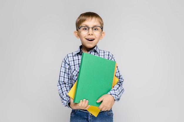 Un niño encantador con una camisa vkletchatoy y jeans claros se alza sobre un fondo gris.