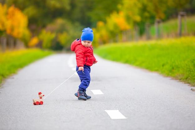 Niño encantador con juguete de madera o patito en una cuerda en el exterior