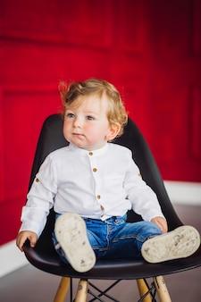 Niño encantador se sienta en la silla en una acogedora habitación roja