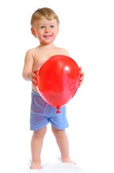 El niño encantador viste pantalones cortos azules y sostiene un globo rojo en las manos.