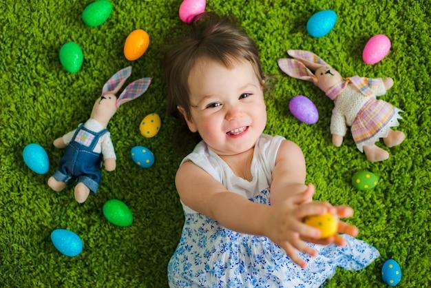 Niño se encuentra en la hierba con huevos de pascua y una liebre