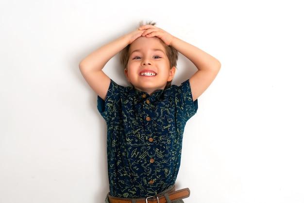 Niño se encuentra sobre un fondo blanco y se ríe.