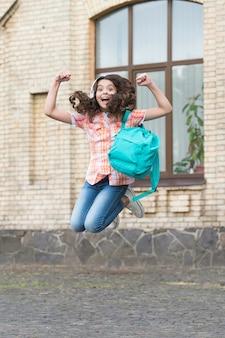 Niño enérgico feliz salta con mochila escolar en estilo casual en el patio de la escuela, vacaciones.