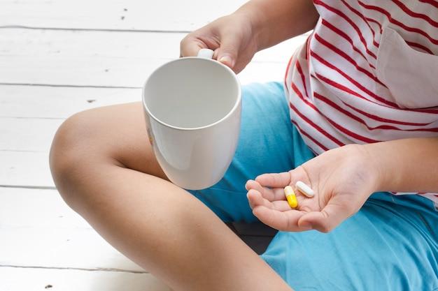 Niño enfermo comiendo pastillas con fondo blanco de madera