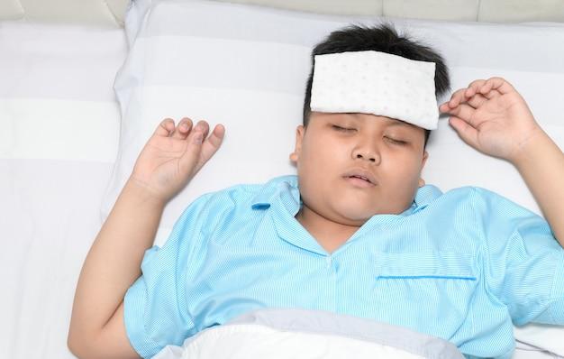 Niño enfermo con fiebre alta acostado en la cama.