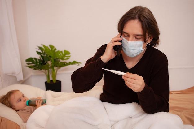 El niño está enfermo, el padre con una máscara revisa la temperatura de su hija.