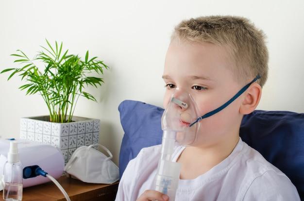 Niño enfermo respirando a través del nebulizador, inhalador para la prevención del tratamiento.