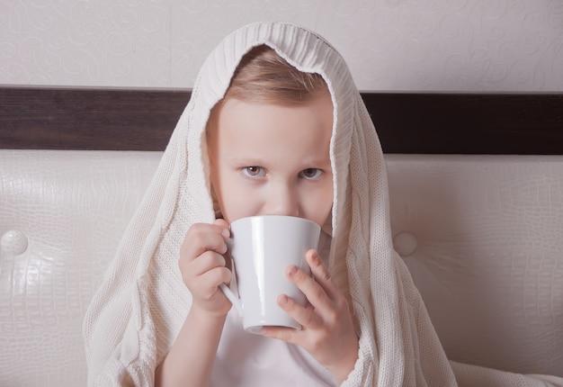 El niño enfermo sentado en una cama y sostiene una taza de té.