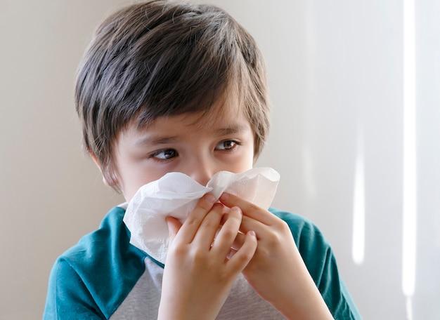 Niño enfermo soplando la nariz en el tejido