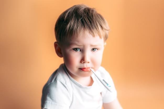 Niño enfermo con un termómetro en la boca con la cara triste sobre fondo naranja