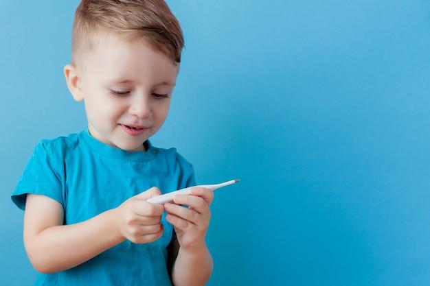 Niño enfermo con un termómetro, midiendo la altura de su fiebre y mirando a la cámara.