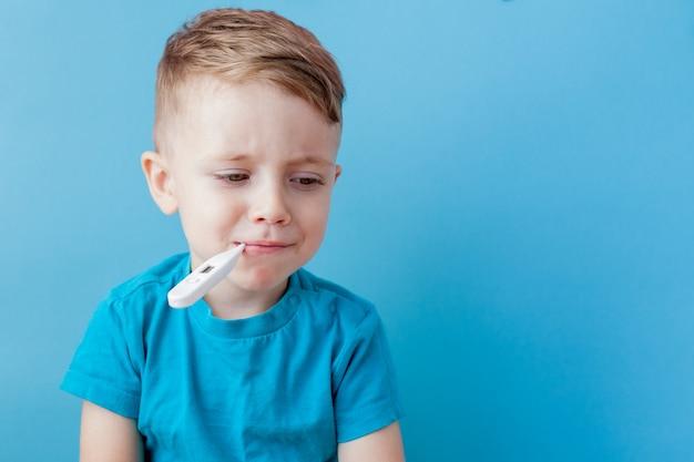 Niño enfermo con un termómetro, midiendo la altura de su fiebre