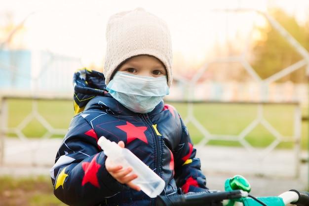 Un niño enmascarado camina por la calle, monta una bicicleta y toma todas las precauciones para prevenir la infección por coronavirus. desinfección de manos y bicicletas con antiséptico.