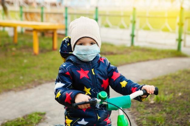 Un niño enmascarado camina por la calle, monta una bicicleta y toma todas las precauciones para prevenir la infección por coronavirus.