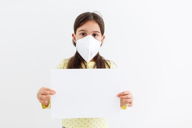 Niño enmascarado: protección contra el virus de la influenza. niña caucásica con máscara para proteger pm2.5. armas biológicas. bebé sobre un fondo gris con espacio de copia. pandemia epidémica.