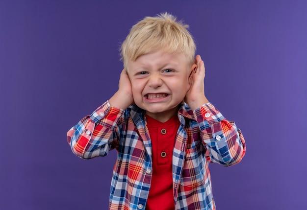 Un niño enojado con cabello rubio vistiendo camisa a cuadros manteniendo las manos en las orejas