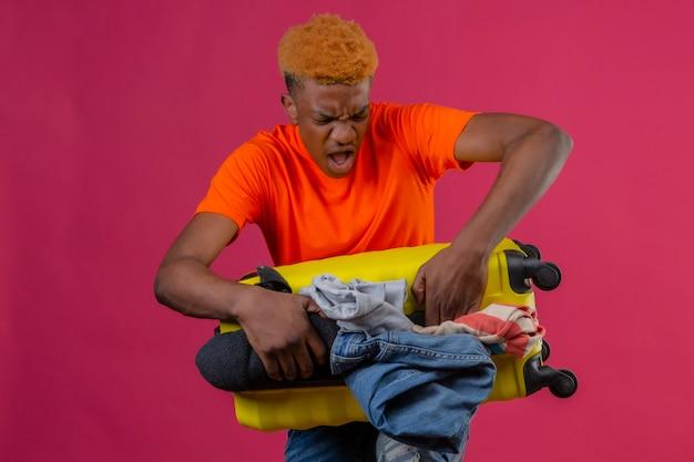 Niño enojado con camiseta naranja de pie con maleta de viaje llena de ropa tratando de cerrarla sobre la pared rosa