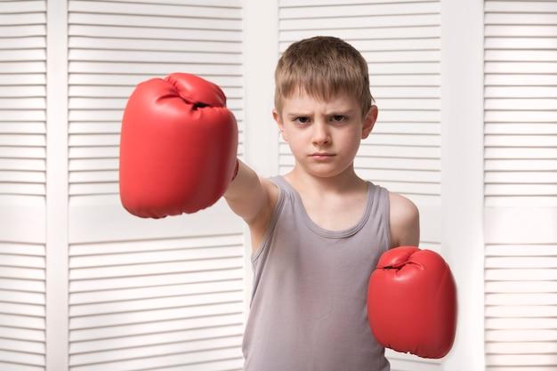 Niño enojado en guantes de boxeo rojos.