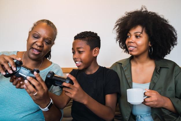 Niño enseñando a la abuela y a la madre a jugar videojuegos.