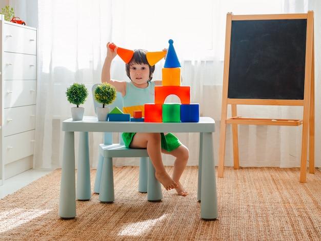 El niño se entrega a jugar en la habitación. preescolar, jardín de infantes, 3 años