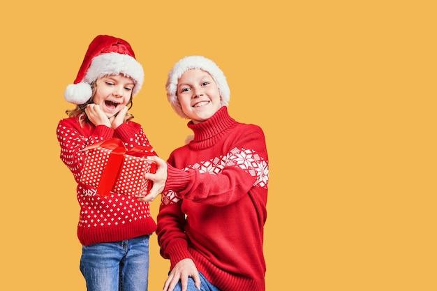 Niño entregando el regalo de navidad a la niña sorprendida