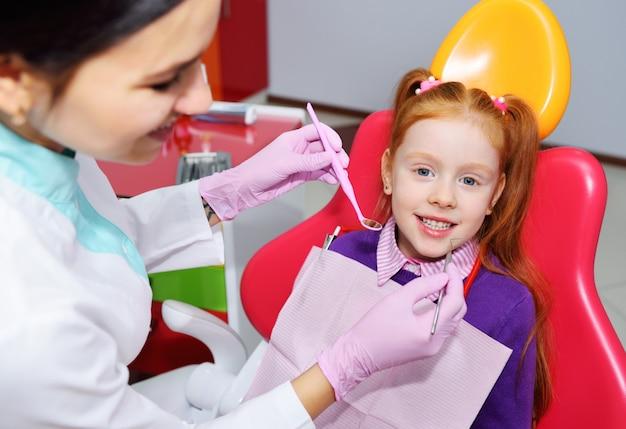 El niño es una niña pelirroja sonriente sentada en una silla dental.