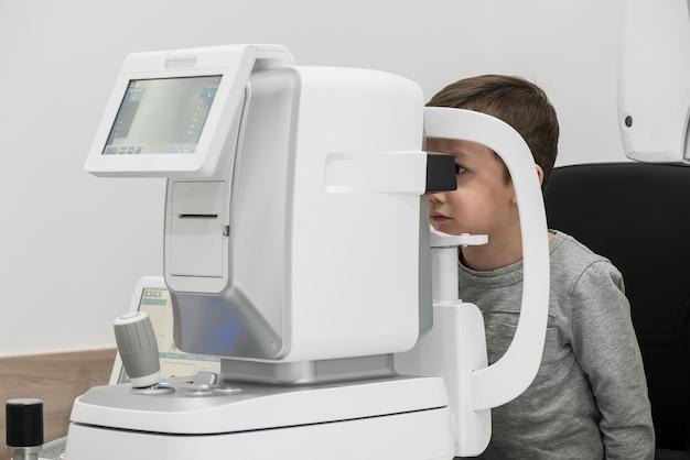 El niño es el paciente a la recepción en el médico oftalmólogo equipo oftalmológico de diagnóstico