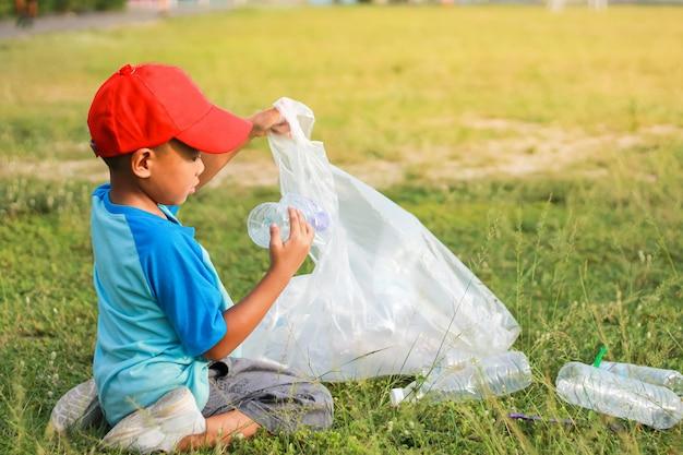 Un niño es voluntario para limpiar el piso del campo. recogió muchas botellas de plástico y paja en el suelo.