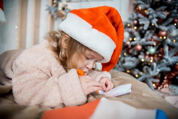 Niño escribiendo la carta a la carta de santa claus con sombrero rojo. familia en navidad. luminoso salón con komin en nochevieja. acogedora y cálida noche de invierno en casa