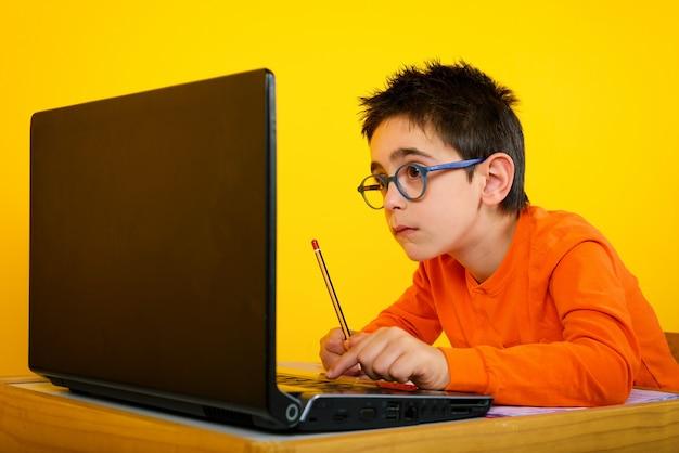 Niño escucha una lección remota con la maestra de la escuela debido a la pandemia de covid-19 en amarillo