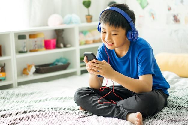 Niño escuchando música en la cama en el dormitorio para relajarse