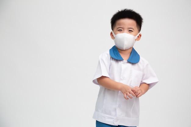 Niño de escuela asiática con mascarilla aislada