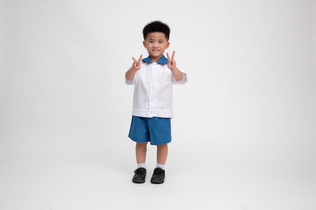 Niño de escuela asiática muestra dos dedos signo aislado