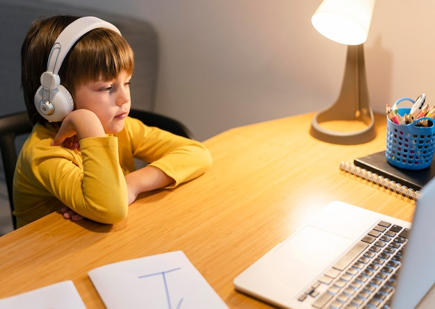 Niño de escuela en camisa amarilla tomando clases virtuales de alta vista
