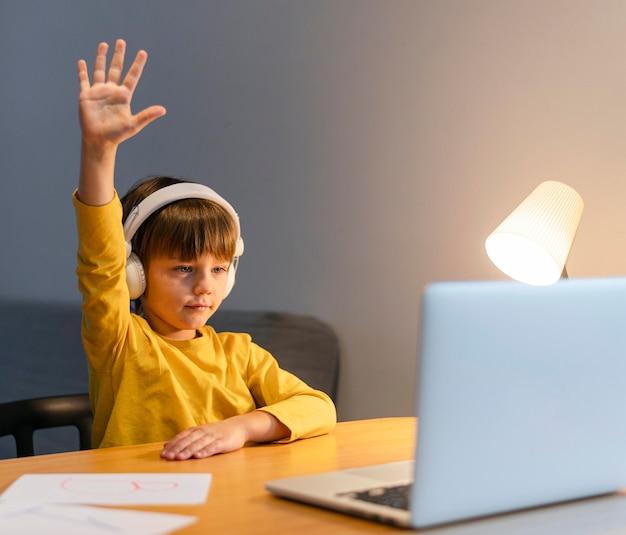 Niño de escuela en camisa amarilla tomando clases virtuales y levantando la mano
