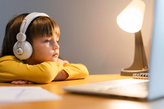 Niño de escuela en camisa amarilla tomando clases virtuales
