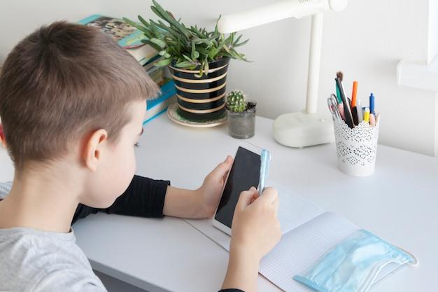 Niño en la escuela en casa con un teléfono inteligente en sus manos y una máscara médica. concepto de cuarentena de coronavirus