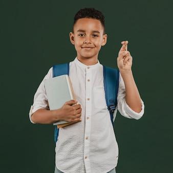 Niño de escuela cruzando los dedos