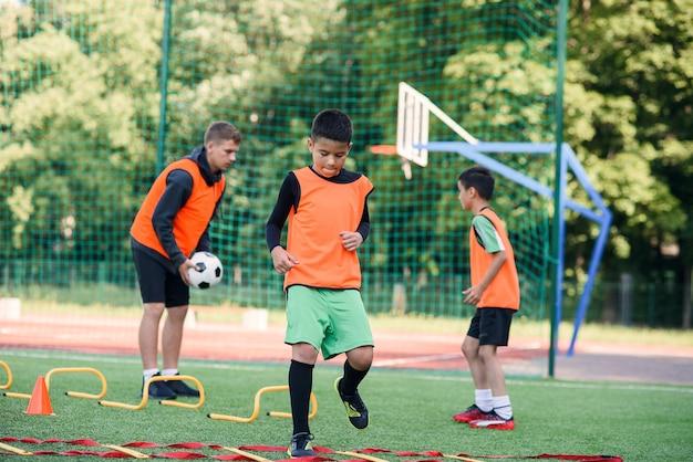 Niño de escuela ejecutando ejercicios de escalera en el césped durante el campamento de verano de fútbol