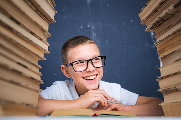 Niño de escuela con gafas sentado entre dos pilas de libros y apartar la mirada de la cámara sonriendo.