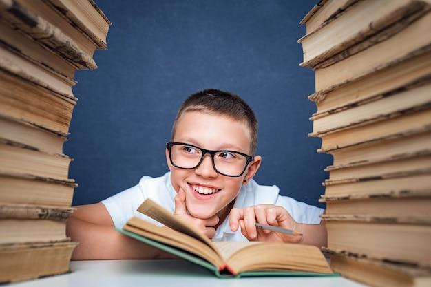 Niño de escuela con gafas sentado entre dos pilas de libros y apartar la mirada de la cámara sonriendo