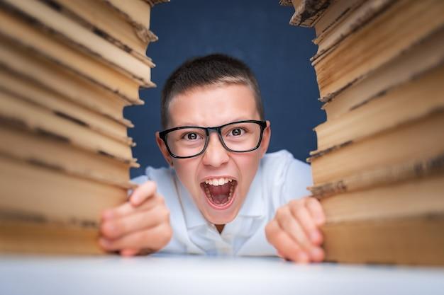 Niño de escuela con gafas sentado entre dos pilas de libros y mira a cámara.
