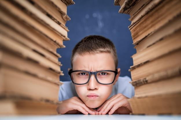 Niño de escuela con gafas sentado entre dos pilas de libros y mirar a cámara infló las mejillas.