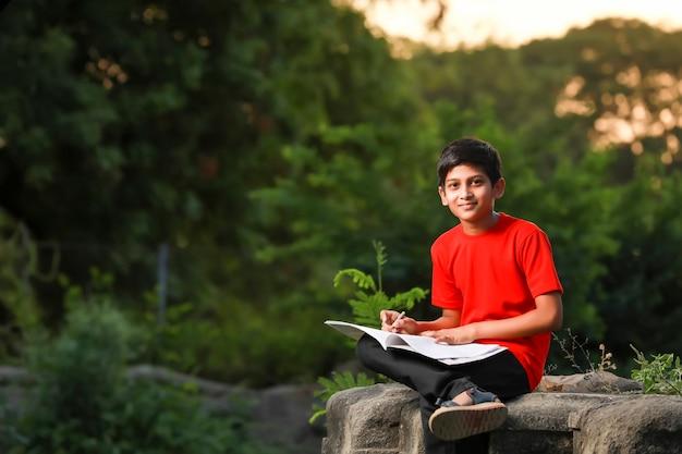 Niño de la escuela india con cuaderno y estudiar en casa