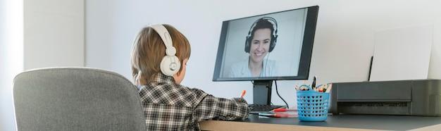 Niño de la escuela en el interior tomando cursos en línea