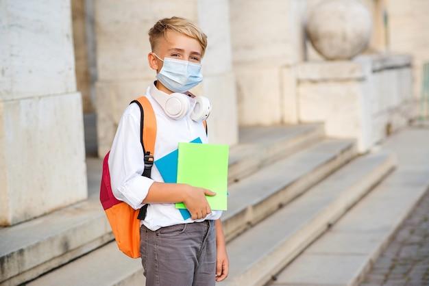 Niño de escuela con mascarilla durante el brote del virus corona