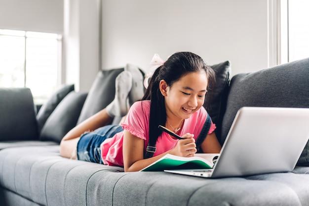 Niño de la escuela niña aprendiendo y mirando la computadora portátil haciendo la tarea estudiando el conocimiento con el sistema de aprendizaje en línea de educación en línea. videoconferencia para niños con el profesor tutor en casa