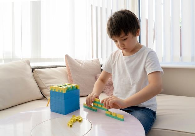 Niño de la escuela con número de conteo de bloques de plástico