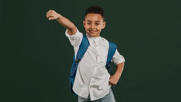Niño de escuela de pie en una posición de superhéroe