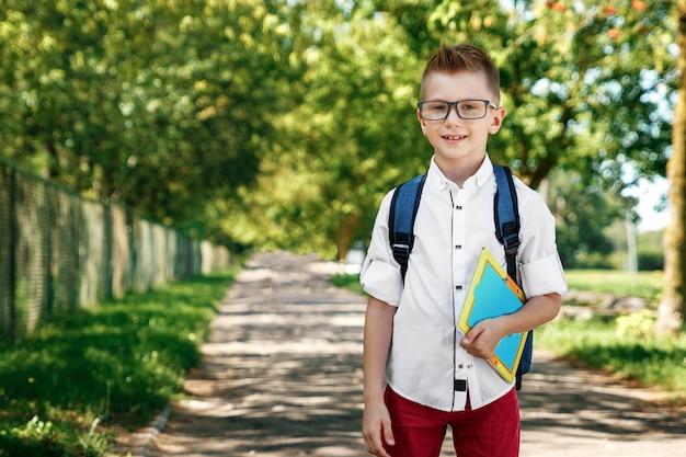 Un niño de una escuela primaria con una mochila en la calle.
